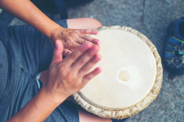 People hands playing music at djembe drums, vintage filter image