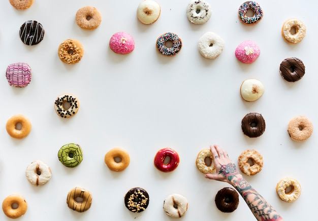 People hands reach for doughnuts