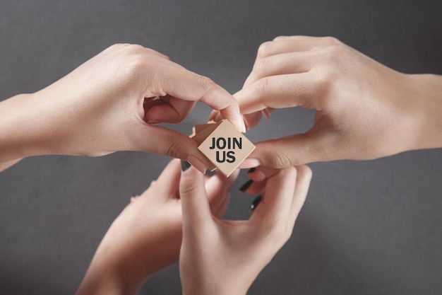 People hands showing join us text on wooden cube