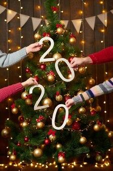 Люди руки показаны числа на елке