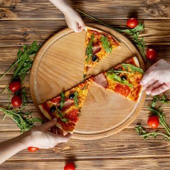 ピザの最後のスライスを取る人の手。木製の背景の上にピザと手がクローズアップ。