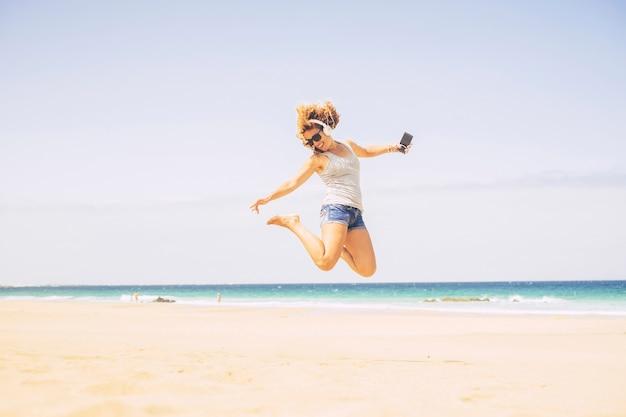 人々はビーチで夏休みの休暇のレジャー活動のコンセプトを喜ばせます-若いクレイジーな美しいブロンドの女性は、バックグラウンドで海と電話とヘッドフォンでジャンプします