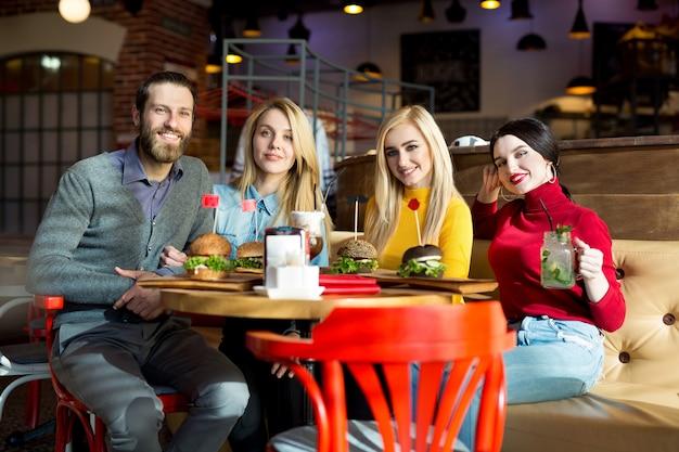 Люди вместе обедают за столиком в кафе. счастливые друзья едят гамбургеры и пьют коктейли в ресторане.