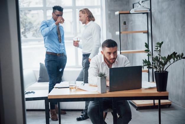 人々はバックグラウンドで議論をしています。青年実業家はラップトップの前の椅子に座って、レポートを操作します