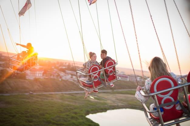 Люди развлекаются, наслаждаясь воздушной каруселью в парке развлечений.
