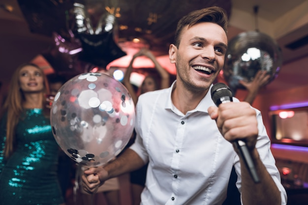 People have fun in a nightclub and sing in karaoke