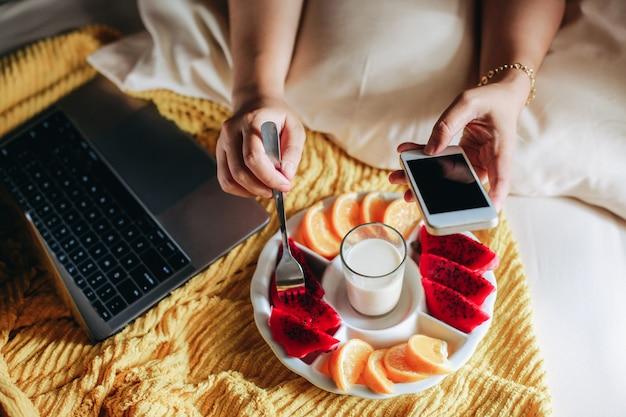 침대에서 노트북으로 작업하는 동안 아침을 먹는 사람들