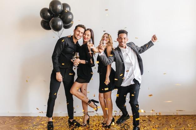 Люди веселятся на вечеринке с черными шарами и конфетти