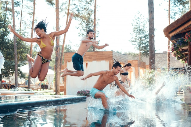 People having fun by jumping from poolside into water