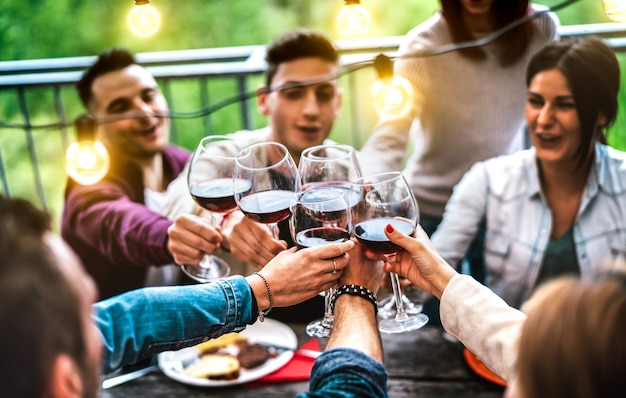People having fun at farm house after sunset - happy friends toasting red wine at restaurant under bulb string light - life style concept with men and women drinking at barbeque reunion on warm filter