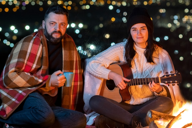 People having fun sitting near bonfire outdoors at night playing guitar