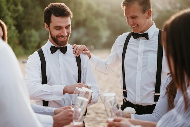 ビーチでの結婚式で飲み物を飲む人