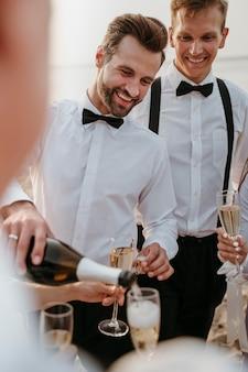 Persone che bevono qualcosa a un matrimonio sulla spiaggia