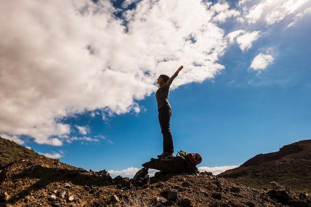 健康的なアウトドアレジャー活動で成功している人々-山でのトレッキングと冒険-自由を楽しんでいる両手を広げて立っている女性-背景の青い空