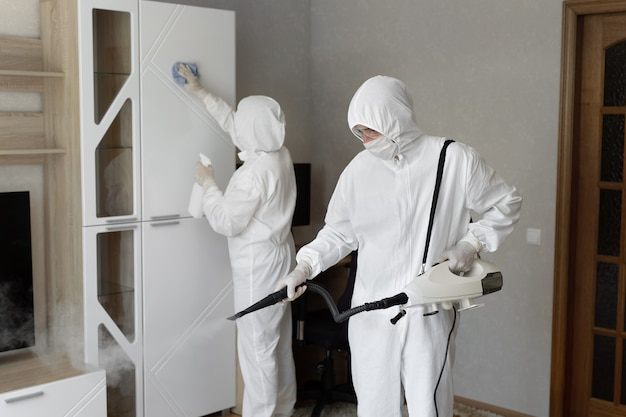 People in hazmats making disinfection in flat