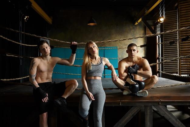 人、健康、活動、運動。屋内でポーズをとる3人のフィットする白人アスリート:筋肉質の裸の胴体を持つ2人の男性の間のボクシングのリングに座っている灰色の服を着たスタイリッシュなブロンドの女の子