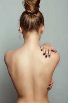 사람, 건강 및 생활 방식 개념 - 회색 배경에 아름다운 여성의 몸. 날씬한 그을린 여자의 몸. 여성의 뜨거운 섹시한 몸과 가슴에 손의 근접 촬영. 뷰티 개념입니다.