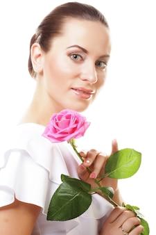 Концепция людей, здоровья и спа: красивая молодая женщина с розовой розой