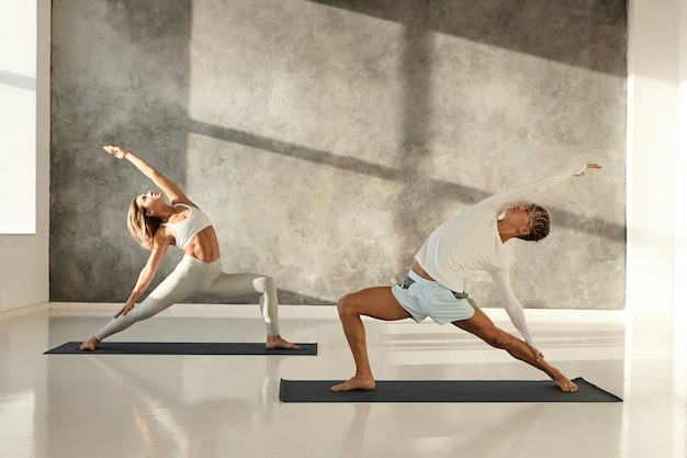 사람, 건강, 스포츠, 웰빙 및 활동 개념. 레깅스를 입고 금발 여성과 요가 아사나를하고 맨발 매트에 서있는 반바지를 입은 젊은 남성의 솔직한 샷
