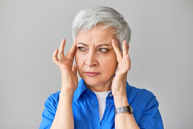 People, health, stress, age and maturity concept. isolated shot of frustrated frowning european fifty year old woman having high blood pressure, massaging temples to soothe intolerable pain