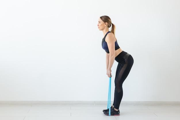 人々、健康的でスポーツのコンセプト-バンドでしゃがむスポーツ服を着た女性にフィットします。