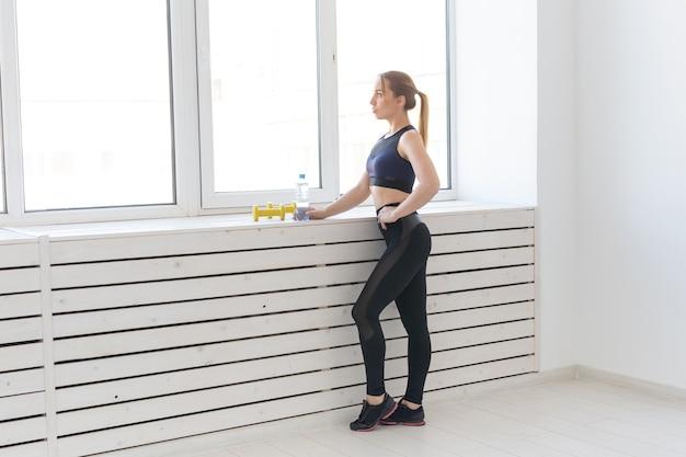 人々、健康とスポーツの概念-窓の近くに水のボトルとダンベルを持つフィットネス女性の肖像画。