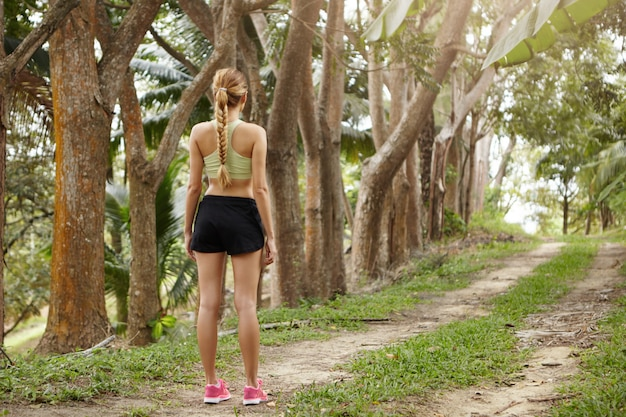 People and healthy lifestyle concept. beautiful fit girl with braid wearing running outfit resting after workout session standing on trail in forest.