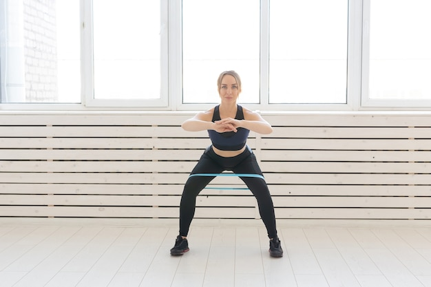 People, healthy and sport concept - fit woman in sports clothes squatting with band.