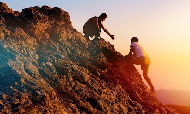 助け合う人々が山でハイキング