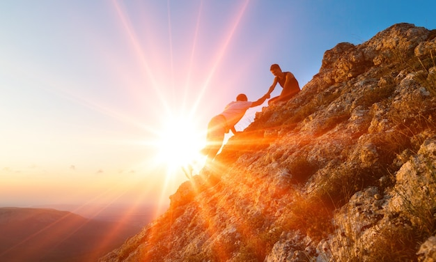 산에서 하이킹을 서로 돕는 사람들