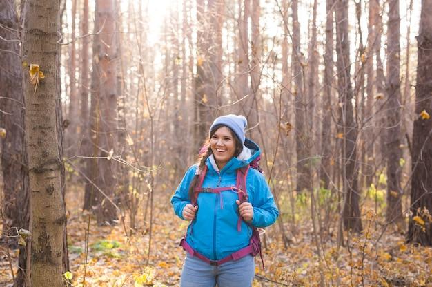 사람, 하이킹, 자연 개념 - 가을 숲을 걷는 여성 관광객.