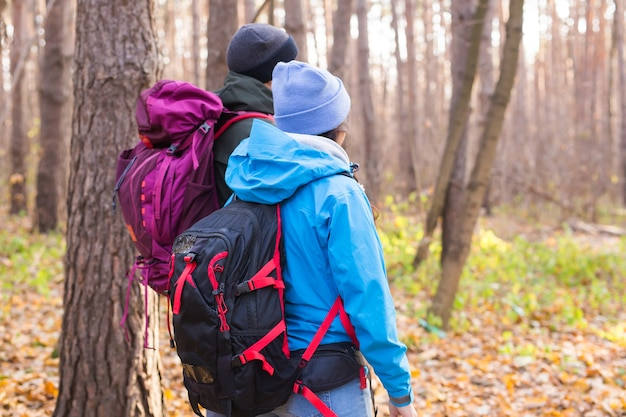 People, hike, tourism and nature concept - couple tourist hiking in autumn forest, back view