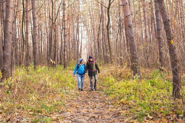 People, hike, tourism and nature concept - couple tourist hiking in autumn forest