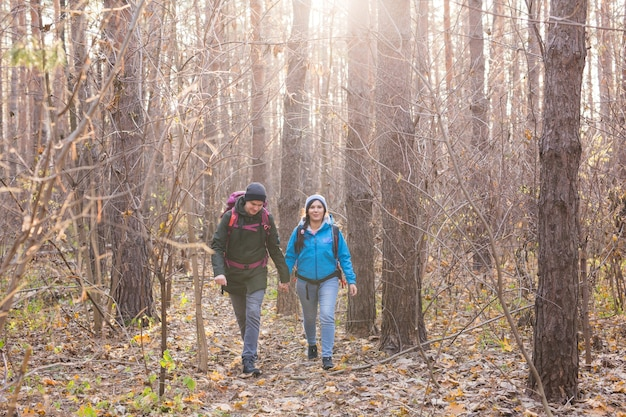 People hike tourism and nature concept  couple tourist hiking in autumn forest