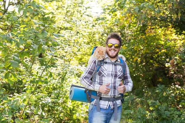 People, hike, tourism and nature concept - man with his cat in the forest