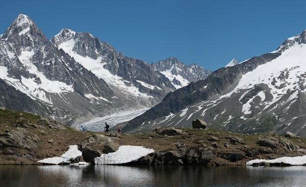 Люди походы и походы по озеру в горах с ледником