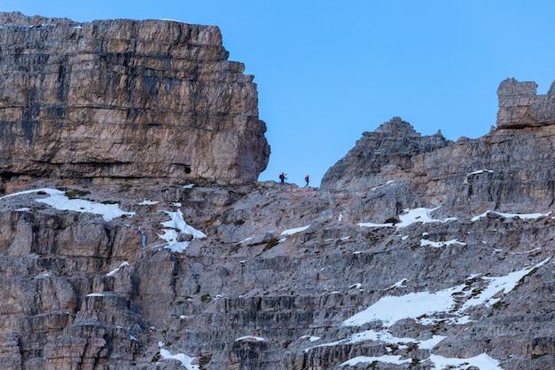 イタリアアルプスの岩でハイキングする人々