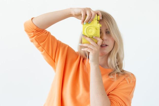 人々、趣味、興味の概念-美しい少女は白い背景の上の黄色のレトロなカメラを保持します