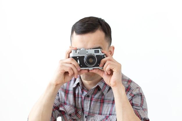 Концепция хобби и досуга людей - молодой хипстерский мужчина, использующий свою старинную камеру на белой поверхности