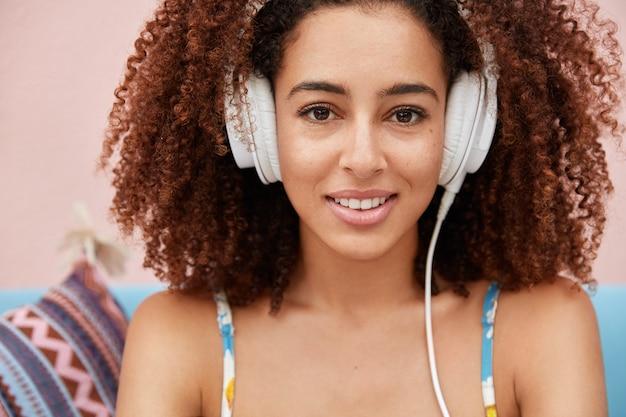 Люди, хобби и молодежное понятие. милая молодая афроамериканка с вьющимися густыми темными волосами слушает любимую популярную музыку в современных наушниках.