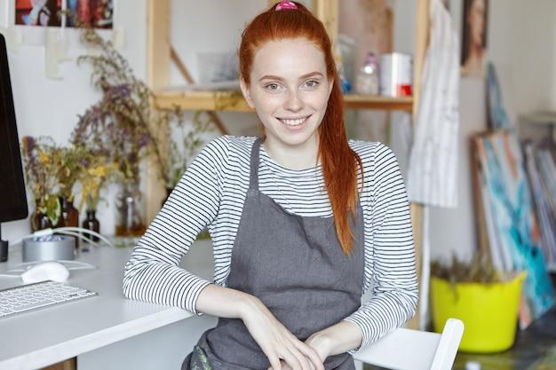 人、趣味、創造的な仕事および職業の概念。ドライフラワーと彼女のワークショップでリラックスした素敵な笑顔の魅力的な赤い髪の若い女性の花屋の肖像画