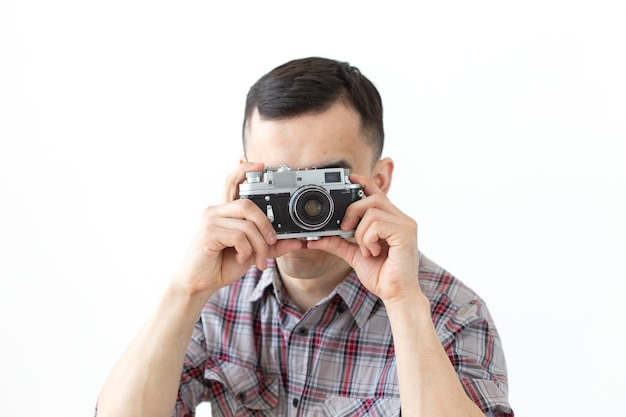 People hobby and leisure concept - young hipster man using his vintage camera on white surface