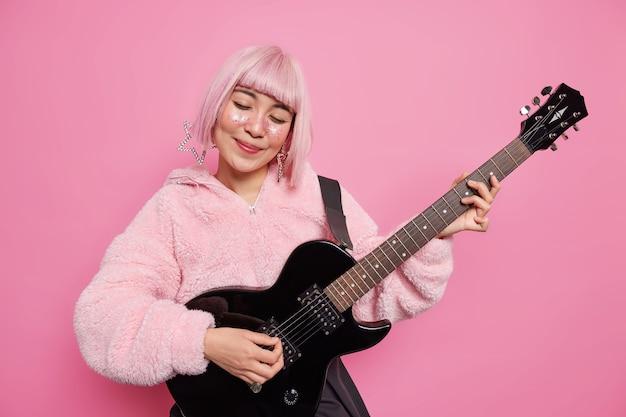 사람들이 취미 음악 개념. 기뻐 세련된 핑크 머리 재능있는 여성 뮤지션이 어쿠스틱 기타에서 록앤롤 노래를 연주하며 인기 스타가되는 무대에서 공연합니다.