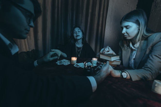 Люди держатся за руки ночью за столом со свечами