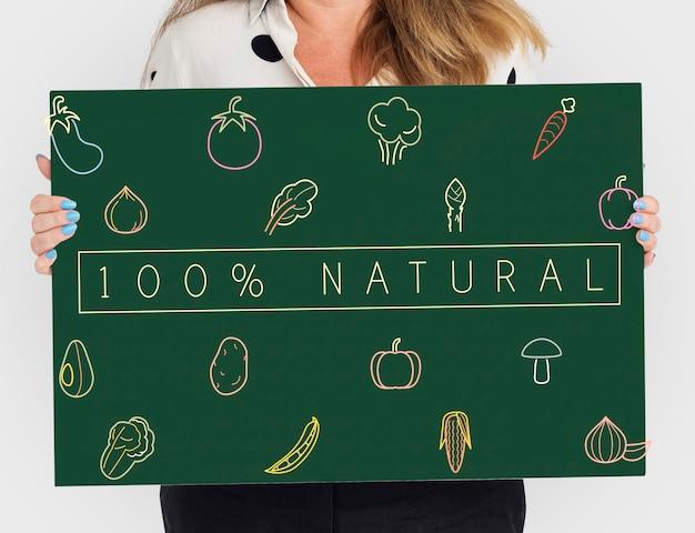 健康的な栄養野菜についてのボードを持っている人々
