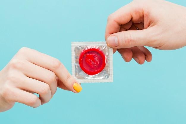 赤いコンドームを持っている人