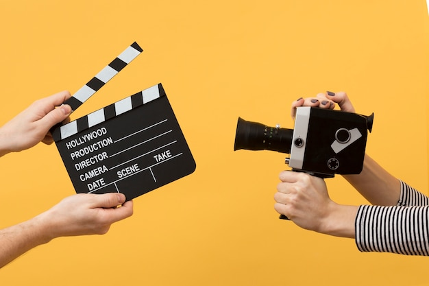 People holding a clapperboard and a film camera