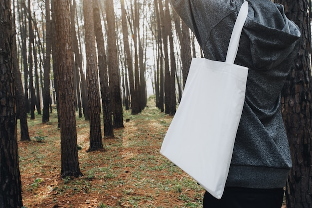 People holding cotton bag for mockup blank in nature background