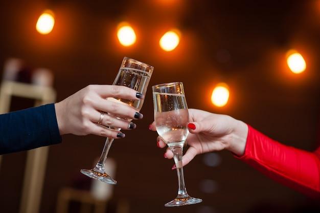 Люди держат бокалы шампанского, делая тост