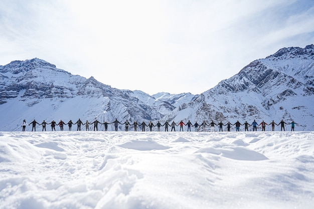 겨울의 배경에 산과 평화의 표시로 손을 잡고있는 사람들